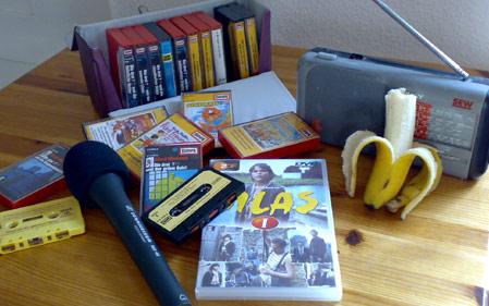 Mein alter Kassettenkoffer, ein kleines Radio, eine Silas-DVD, ein Mikrofon und eine angebissene Banane